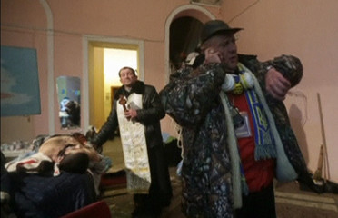 A still image from a video footage shows a priest standing near the body of a man, whom eyewitnesses say was a pro-European protester, inside a makeshift hospital in Kiev