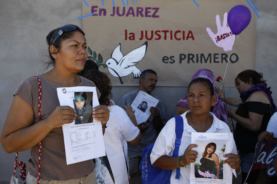 Relatives of missing women hold flyers with information about their loved ones after a rally led by Mexican poet Sicilia to support victims of feminicide in Ciudad Juarez