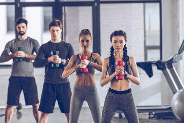 group of athletic young people in sportswear with dumbbells exercising at the gym
