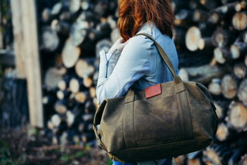 The young girl with a leather bag at a wall from logs.