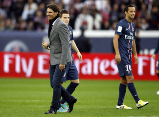 Spain's tennis player Nadal walks past Paris St Germain's Nene and Gameiro before the French Ligue 1 soccer match between Paris Saint Germain and Reims in Paris