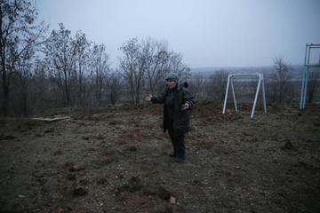 Local resident reacts as she stands next to a crater after shelling in Artemivsk