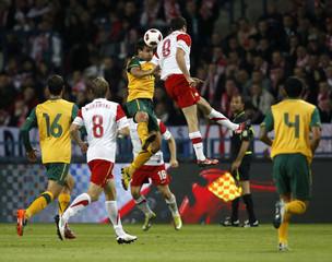 Robert Lewandowski of Poland and Richard Garcia of Australia jump for a ball during an international friendly soccer match in Krakow