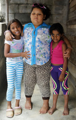 Dana Garcia, 8, poses for a picture with her friends, who are the same age as her, at her home in Medellin