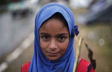 A girl displaced by heavy floods stands outside her temporary shelter on a flyover in Srinagar