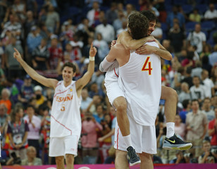 Spain's Navarro jumps in the arms of teammate Gasol as Spain's Fernandez celebrates in the background after their men's basketball semifinal match against Russia at the North Greenwich Arena during the London 2012 Olympic Games