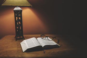 Open Holy Bible On Wood Table With Glasses