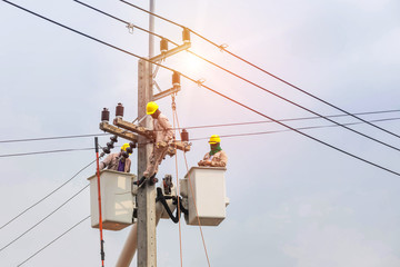 Electricians repairing wire of the power line with bucket hydraulic lifting