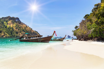 longtail boats with small island in andaman sea under blue sky at krabi Thailand