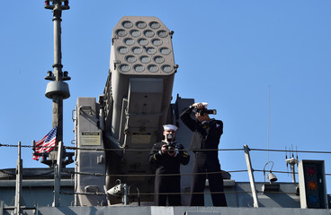 U.S. crew members take pictures on the top of the deck of the USS Fort Worth at a naval port in Busan