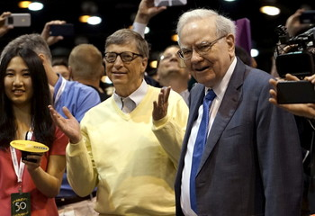Berkshire Hathaway CEO Warren Buffett and Microsoft co-founder Bill Gates react after participating in a newspaper throwing contest prior to the Berkshire annual meeting in Omaha