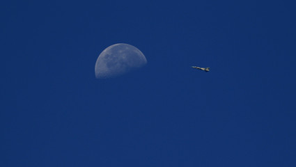 Fighter jet belonging to forces of Syria's President Assad flies in the sky, as the moon is seen in the background, from the town of Morek in Hama province