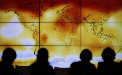 Participants looks at a screen projecting a world map with climate anomalies during the World Climate Change Conference 2015 (COP21) at Le Bourget