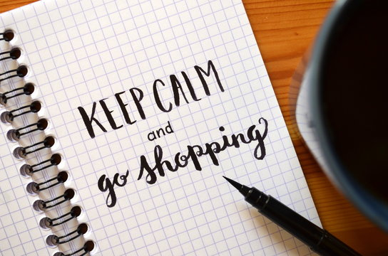 KEEP CALM AND GO SHOPPING written in notebook with cup of coffee on desk