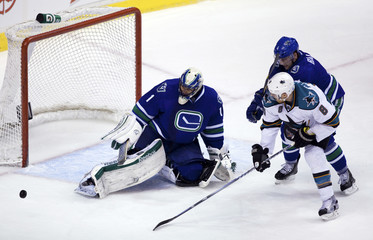 Vancouver Canucks' Ballard fights for the puck against San Jose Sharks' Pavelski in front of Canucks goaltender Luongo during their NHL hockey game in Vancouver