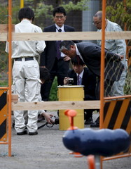 Workers of Tokyo's Toshima ward office and police officers check container holding fragment of unknown object after it was dug up from ground near playground equipment at park in Toshima ward