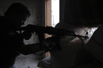 A Free Syrian Army fighter takes up a shooting position in the Salah al-Din neighbourhood of central Aleppo