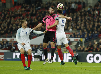 Scotland's Grant Hanley in action with England's Gary Cahill and Eric Dier