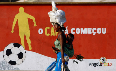 A woman balances a bundle of bread on her head to sell as she carries her child on her back near the Olympic Village in Cabinda