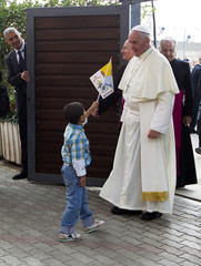 Pope Francis is welcomed by a child as he arrives at the Caritas Reception Center at St. Mary of the Angels, near Assisi