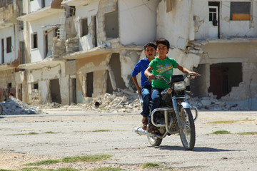 Boys ride a motorcycle near a damaged building during the third day of Eid al-Adha in the rebel controlled city of Idlib