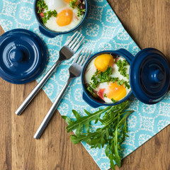 Baked eggs for breakfast in blue ceramic baking molds. Portioned casserole from vegetables and eggs in Italian style. Eggs Kokot. Top view