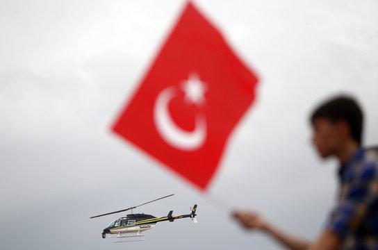 A police helicopter flies past a man waving a Turkish flag as Prime Minister Tayyip Erdogan gives a speech at his rally in Ankara