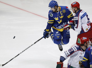 Sweden's Persson fights for the puck with Russia's Nikulin during their Channel One Cup ice hockey game at Megasport arena in Moscow