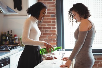 Lesbian couple pouring wine in glass