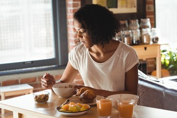 Woman having breakfast while sitting on table at home