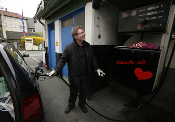 Milz, owner of Germany's oldest and smallest petrol station fills the tank of a car in Essen