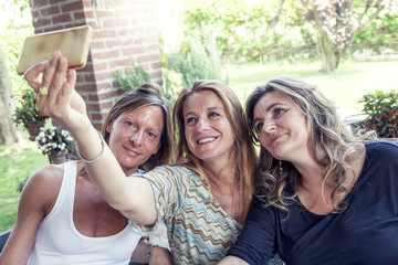 three pretty mature women take a selfie in the countryside