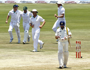 India's Laxman walks off the field after his dismissal as South Africa's players celebrate during their first test cricket match in Pretoria