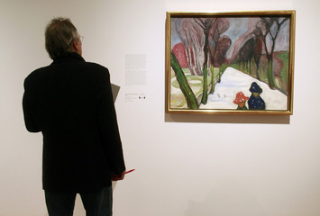 """A visitor looks at the painting """"Avenue in Snow Flurry"""", 1906 by Norwegian artist Edvard Munch presented at an exhibition in Frankfurt"""