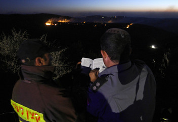 A forest fire on Mount Carmel is seen in the background as Israeli firefighters recite Shabbath prayers near Haifa University
