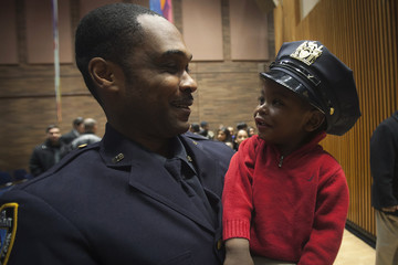 Tristan Glanville tries on his father Jerronie Glanville's hat after he was promoted to the rank of Detective Investigator during a New York Police Department Promotion Ceremony at Police Headquarters in the Manhattan borough of New York