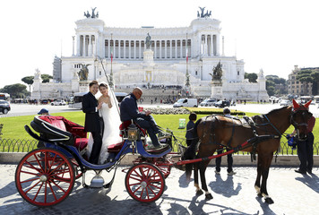 A newly-married Asian couple poses for a photo on a horse-drawn carriage outside Rome's Altar of the Fatherland in central Rome