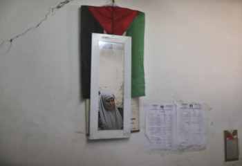Palestinian policewoman loyal to Hamas is reflected in a mirror as she works at her office in Gaza City