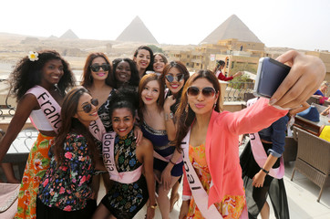 Contestants of Miss ECO Universe take a selfie with pyramids behind, on the outskirts of Cairo