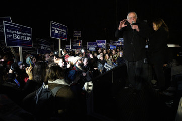 U.S. Democratic presidential candidate Bernie Sanders, with his wife Jane, addressess supporters from the bed of a pickup truck after arriving early morning in Bow