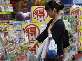 A woman looks at goods outside a drugstore in Tokyo