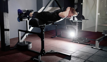 Young man training back muscles. Muscular athlete exercising. Full body length portrait