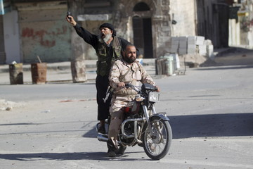 Members of al Qaeda's Nusra Front ride a motorbike as one of them cheers in the northwestern city of Ariha, after a coalition of insurgent groups seized the area in Idlib province