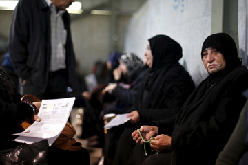 Syrian refugees wait to register at the UNHCR office in Amman, Jordan