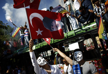 Protesters wearing Guy Fawkes masks wave Turkish national flags bearing a picture of Turkey's founding father Ataturk during a demonstration at Taksim Square in Istanbul