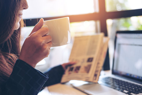 A business woman reading newspaper ,drinking coffee and using laptop in the morning in office
