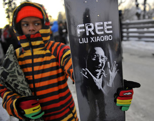 A youth poses with a skateboard displaying a design slogan of Liu outside of the Chinese Embassy in Oslo