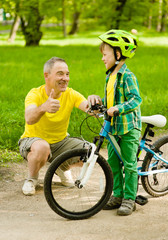 Son and grandfather having fun riding a bike