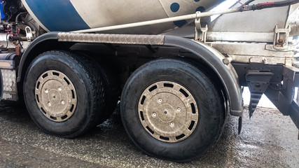 Truck wheels moving on the road. Close up. Delivery of construction material concept background.