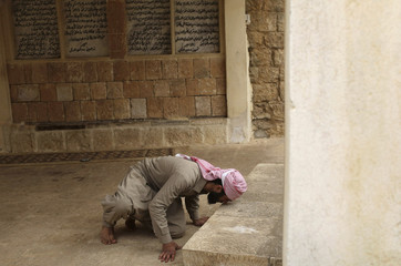 A Yazidi man kisses the ground of a Yazidi temple in Lalish